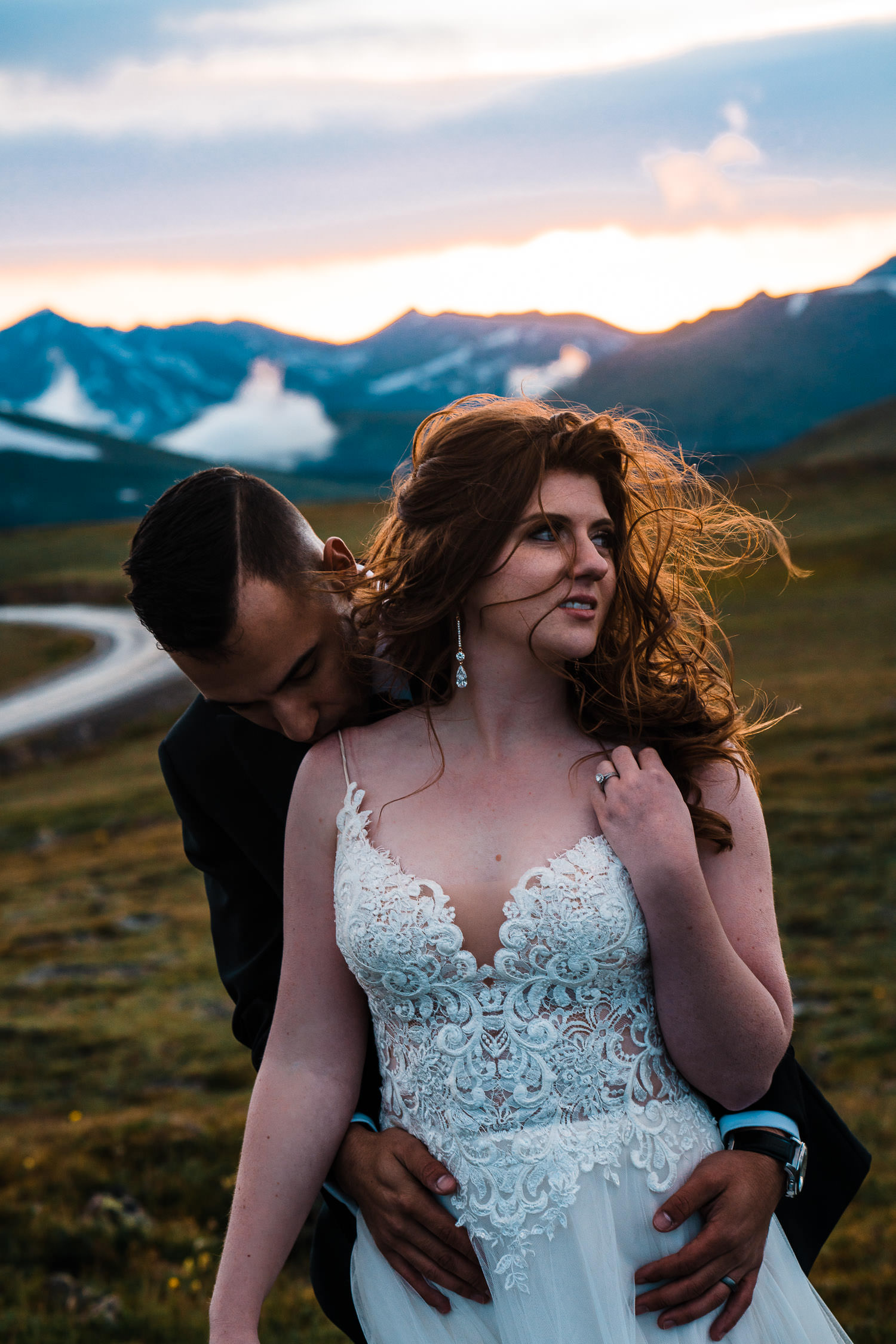 Newlywed couple embraces in the mountains with wind blowing.